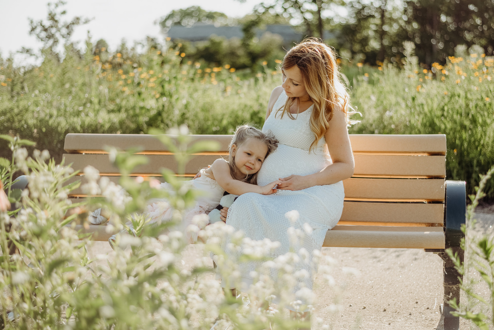pregnant mother hugging daughter on bench by flowers