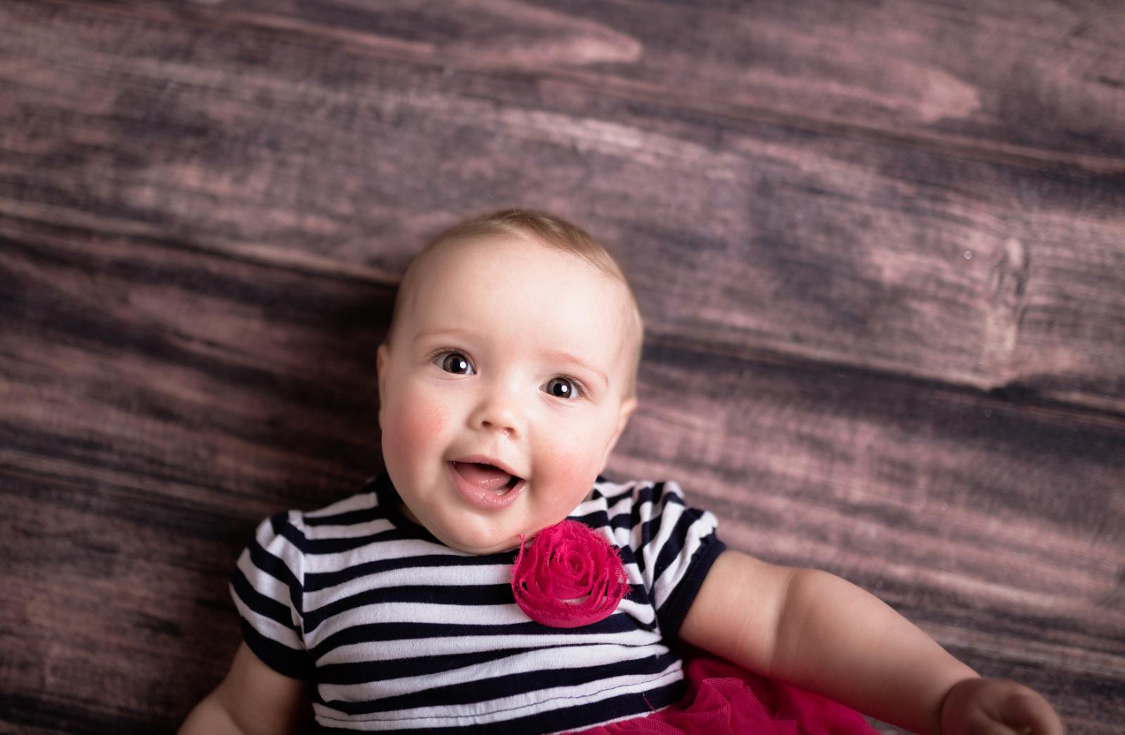 six month baby girl on wood floor