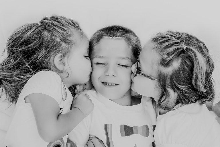 brother being kissed on both cheeks by sisters
