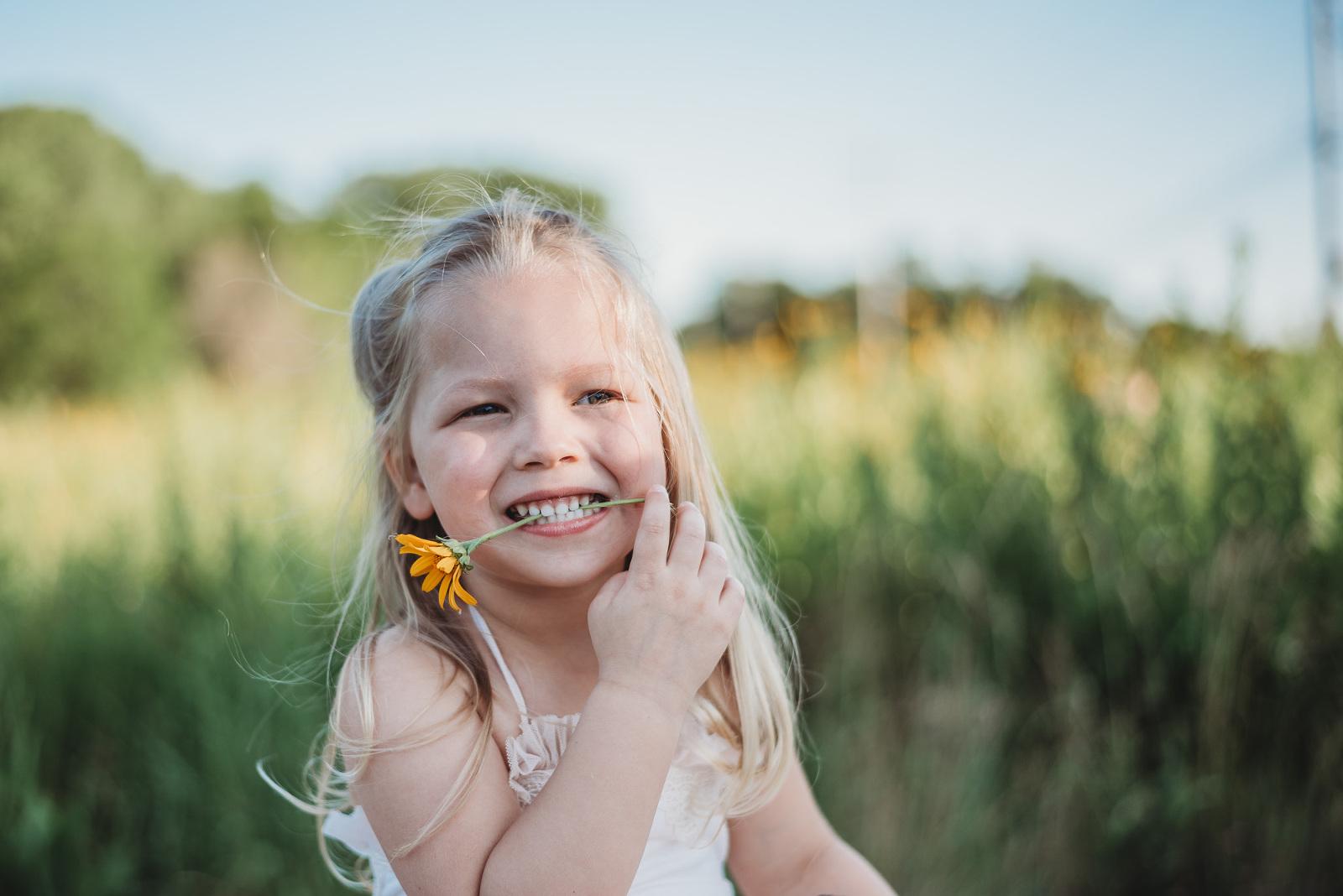 little girl summer flower in mouth