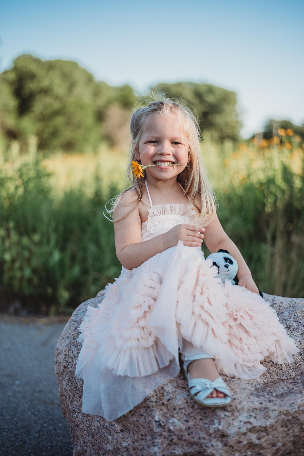 little girl in ruffle dress summer flower in mouth