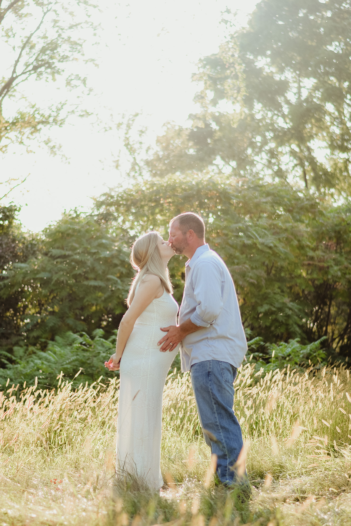 maternity couple kissing in the sun rays