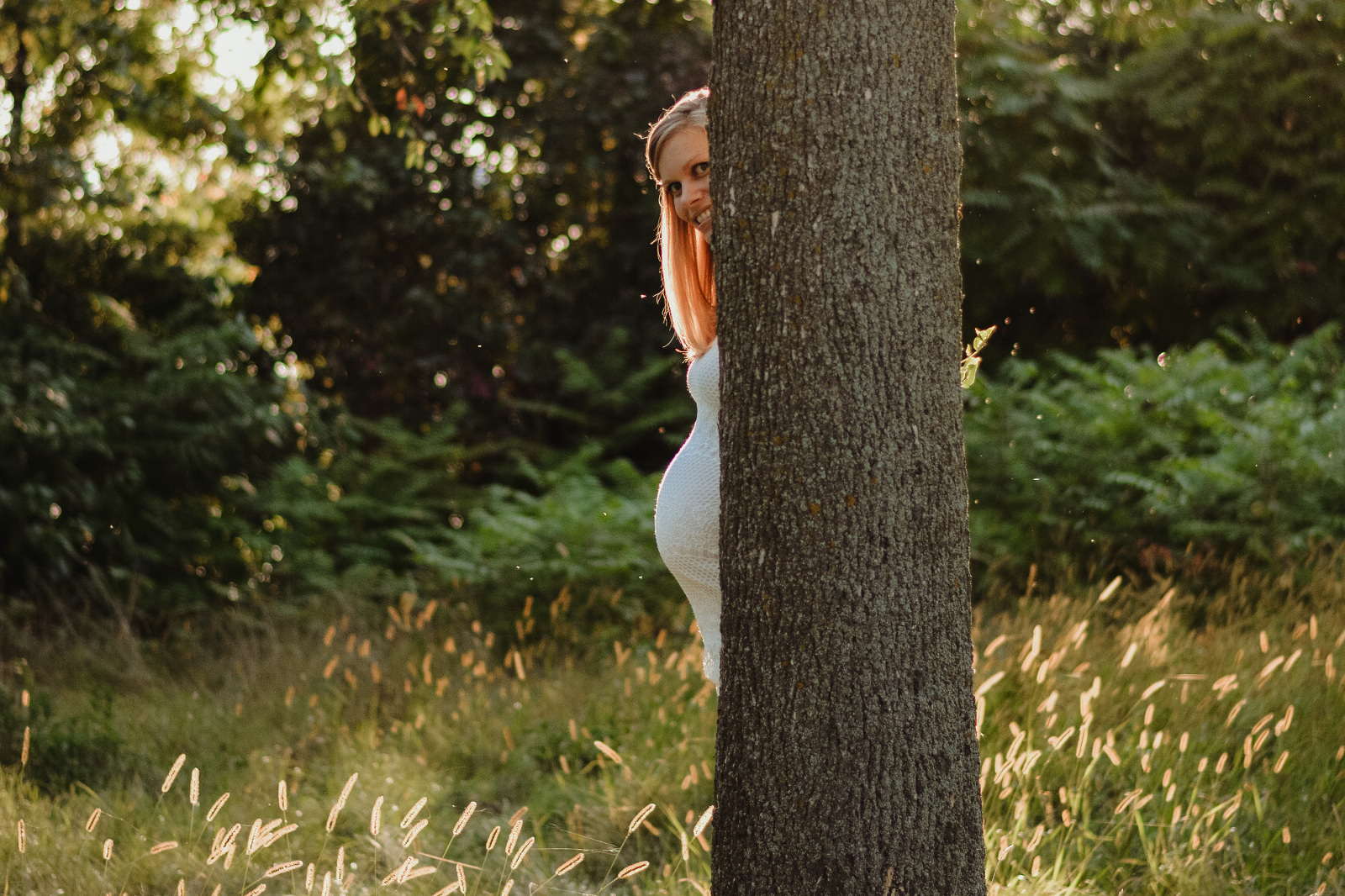 maternity belly hiding behind a tree