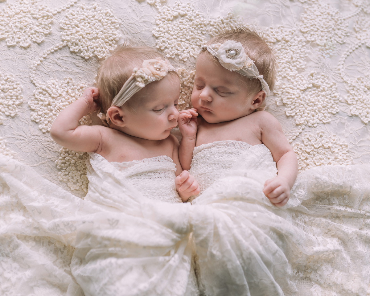 newborn twins baby girl on white