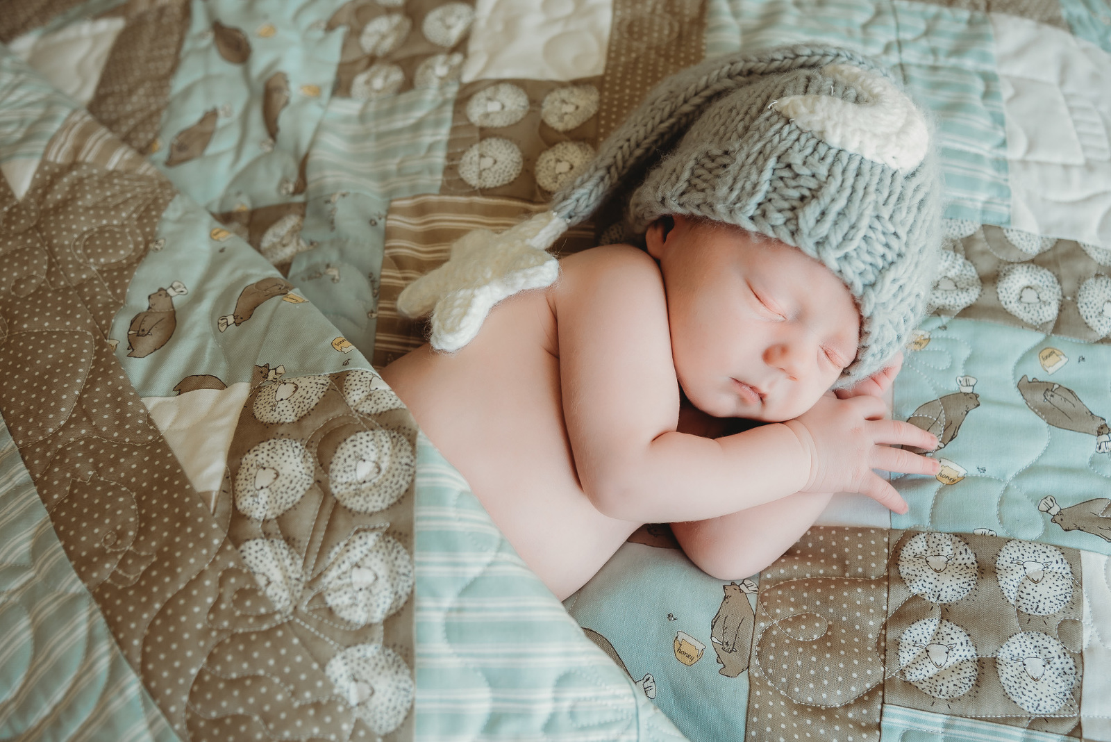 newborn baby boy with sleep cap on quilt