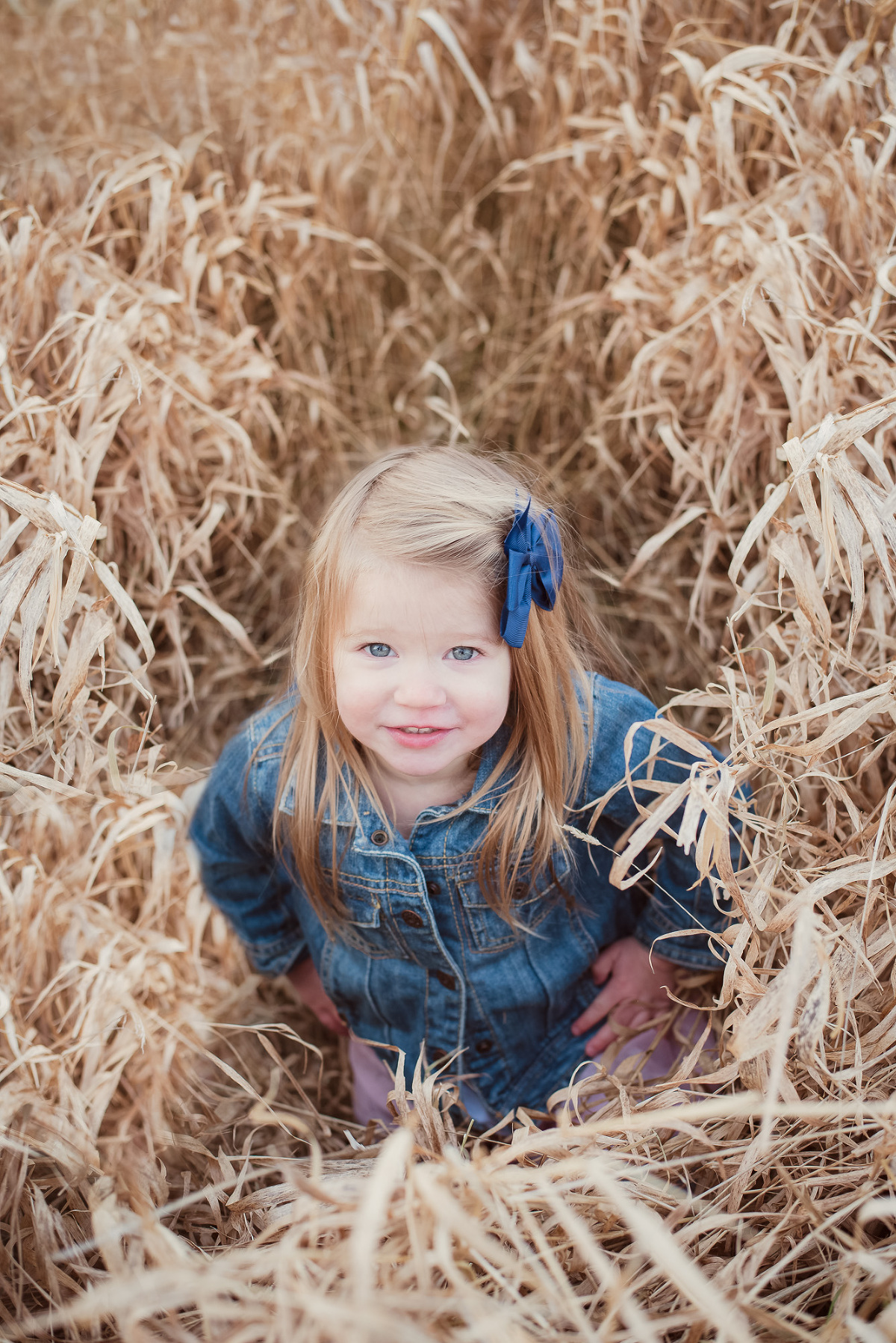 little girl standing in tall grass field