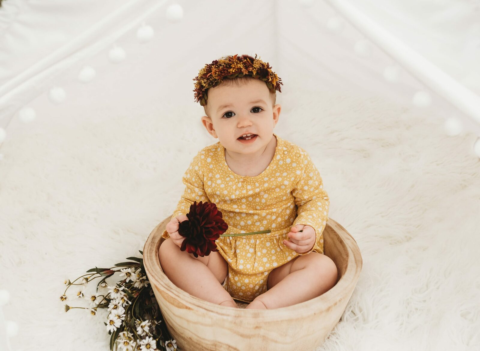 one year old girl in yellow sitting in bowl in white teepee wearing autumn floral halo