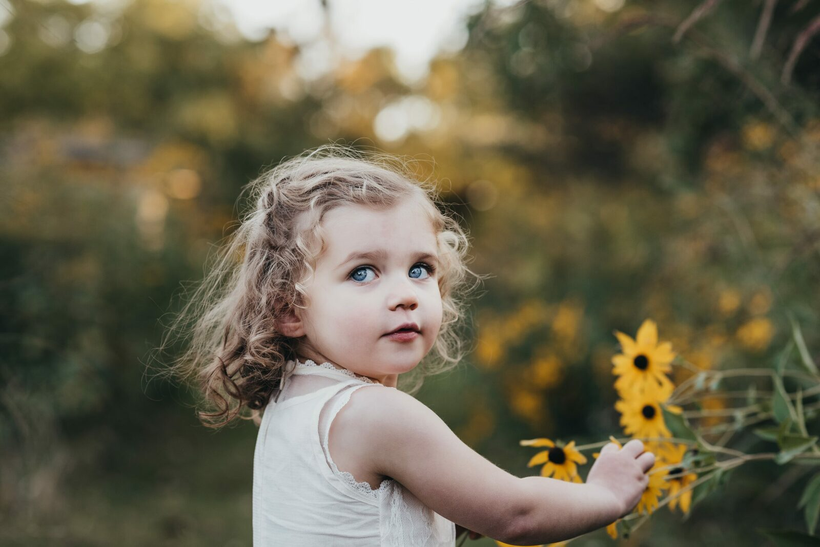 2 year old girl picking a yellow flower looking over her shoulder