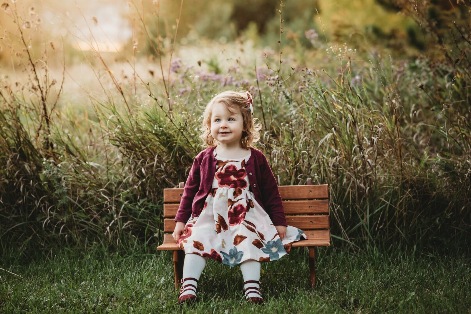 one year old girl on tiny park bench with glowing sunset and grassy field