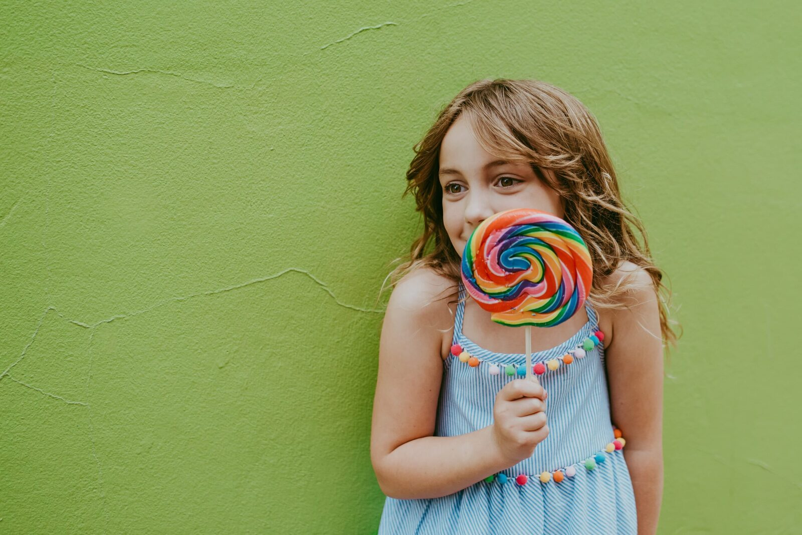 young girl holding a colorful lollipop with green wall in the background