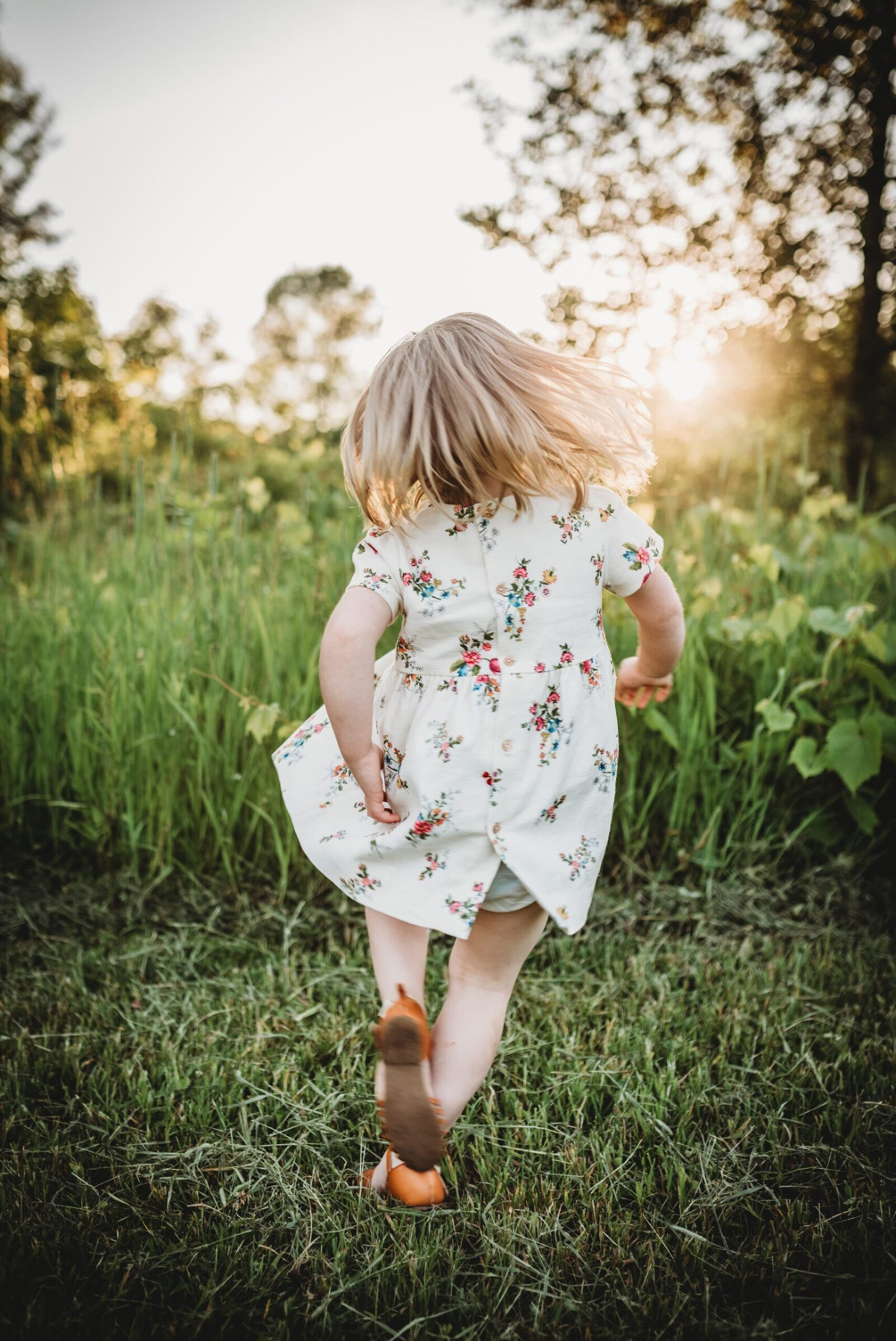 3 year old girl twirling with glowing sun in background