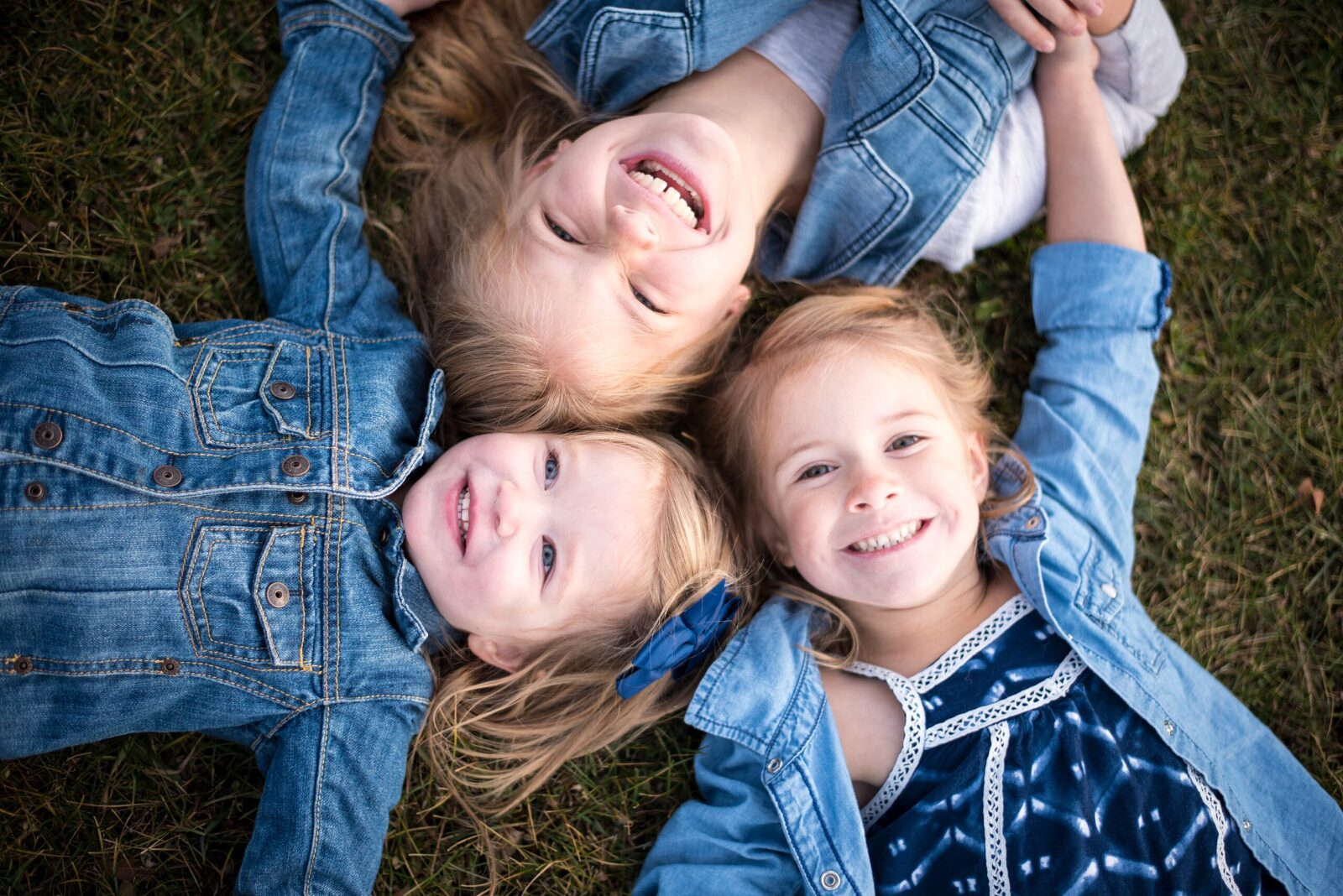 three sisters laying in the grass with heads together smiling and laughing