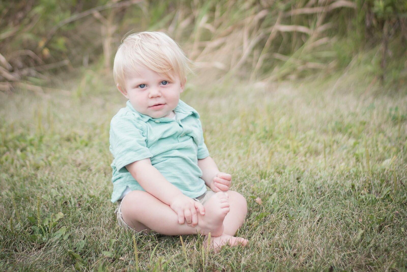 9 month old boy sitting in grassy field