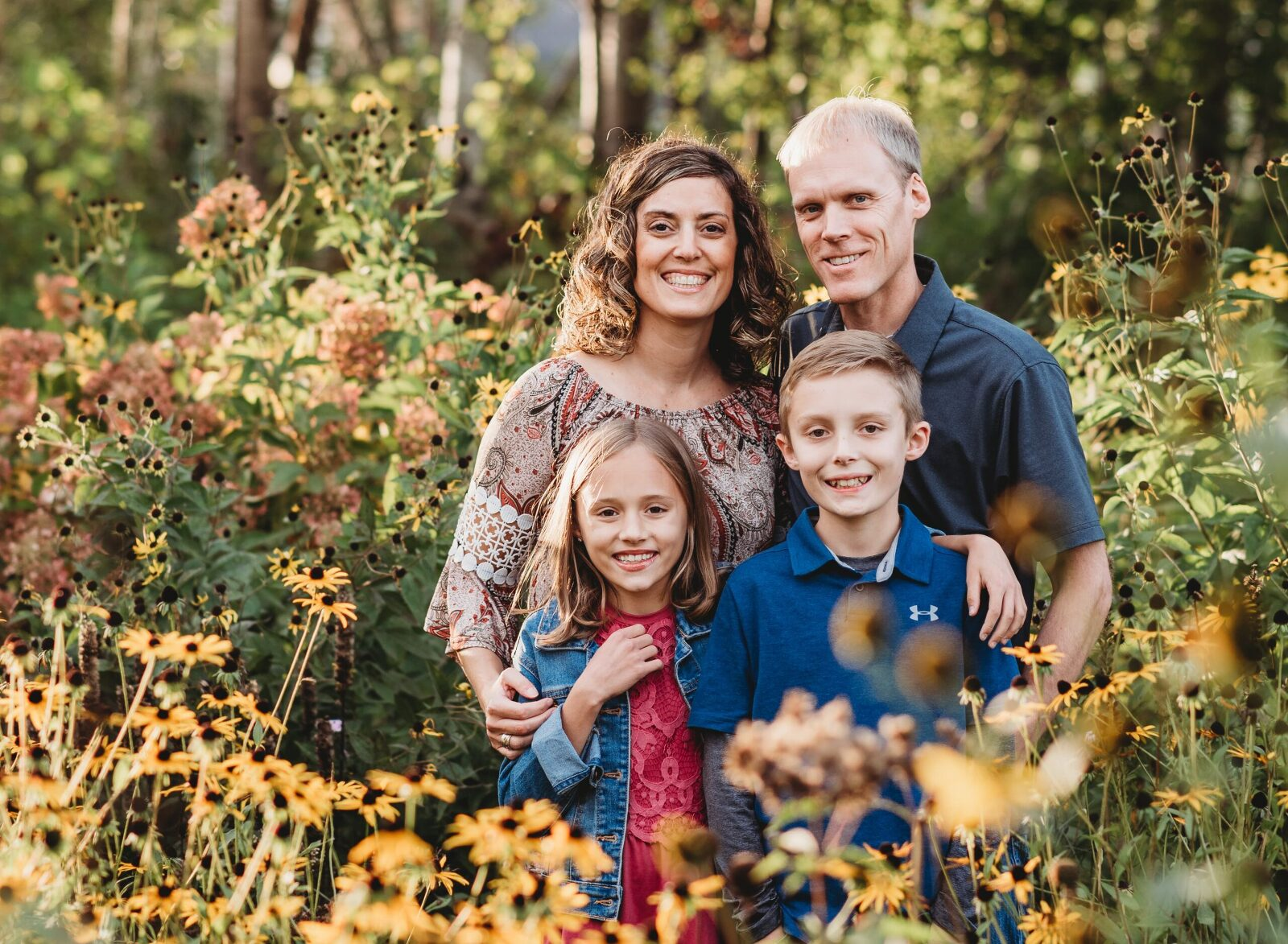 family of four standing standing in a flower garden
