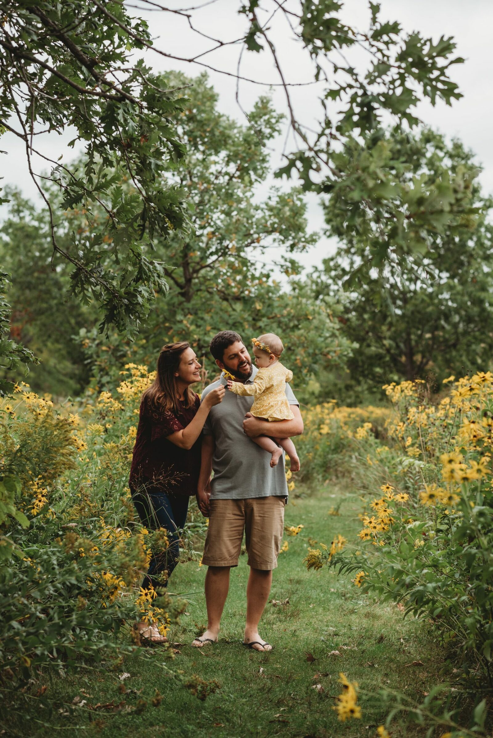young family walking through a field of yellow flowers