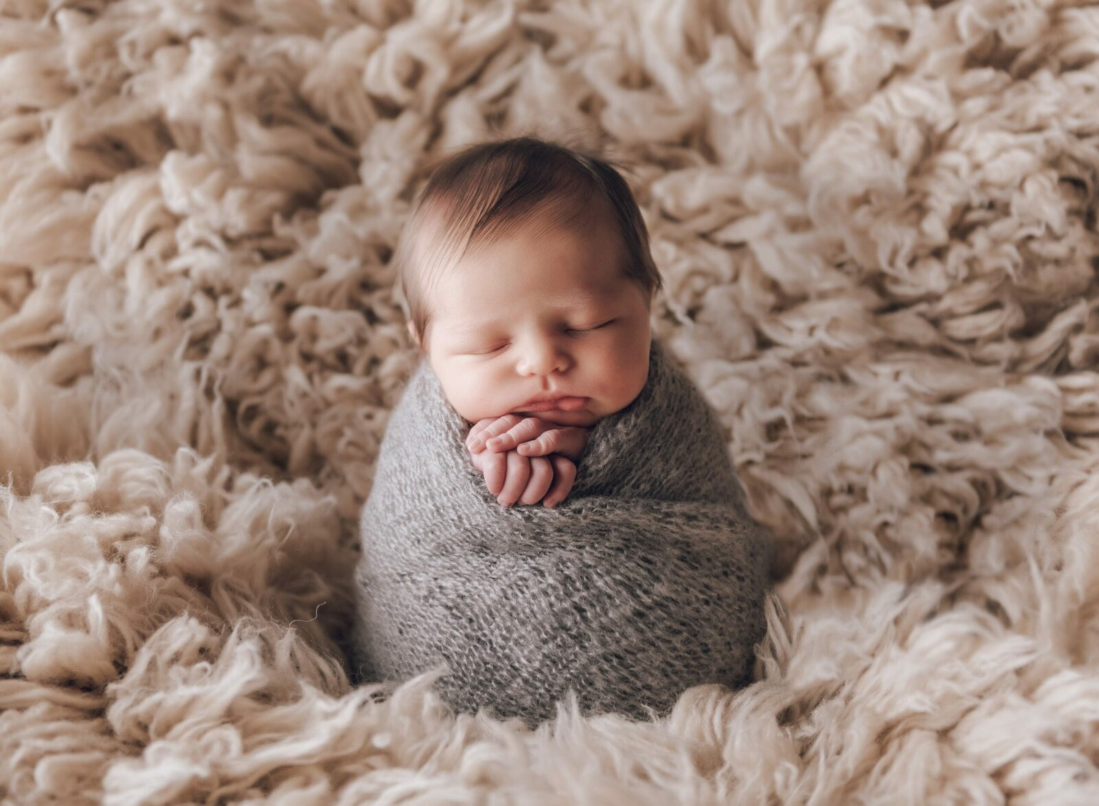 newborn baby boy in potato sack pose on flokati