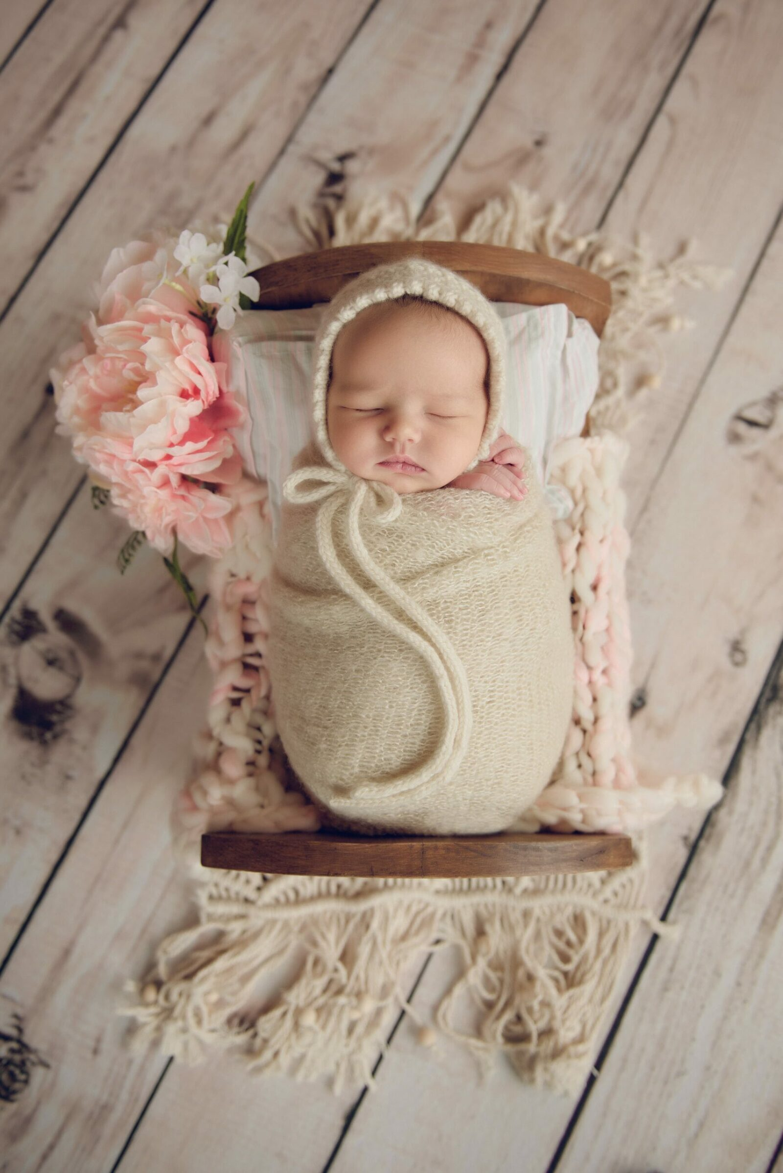 newborn baby girl in cradle with pink flowers wearing a ivory bonnet