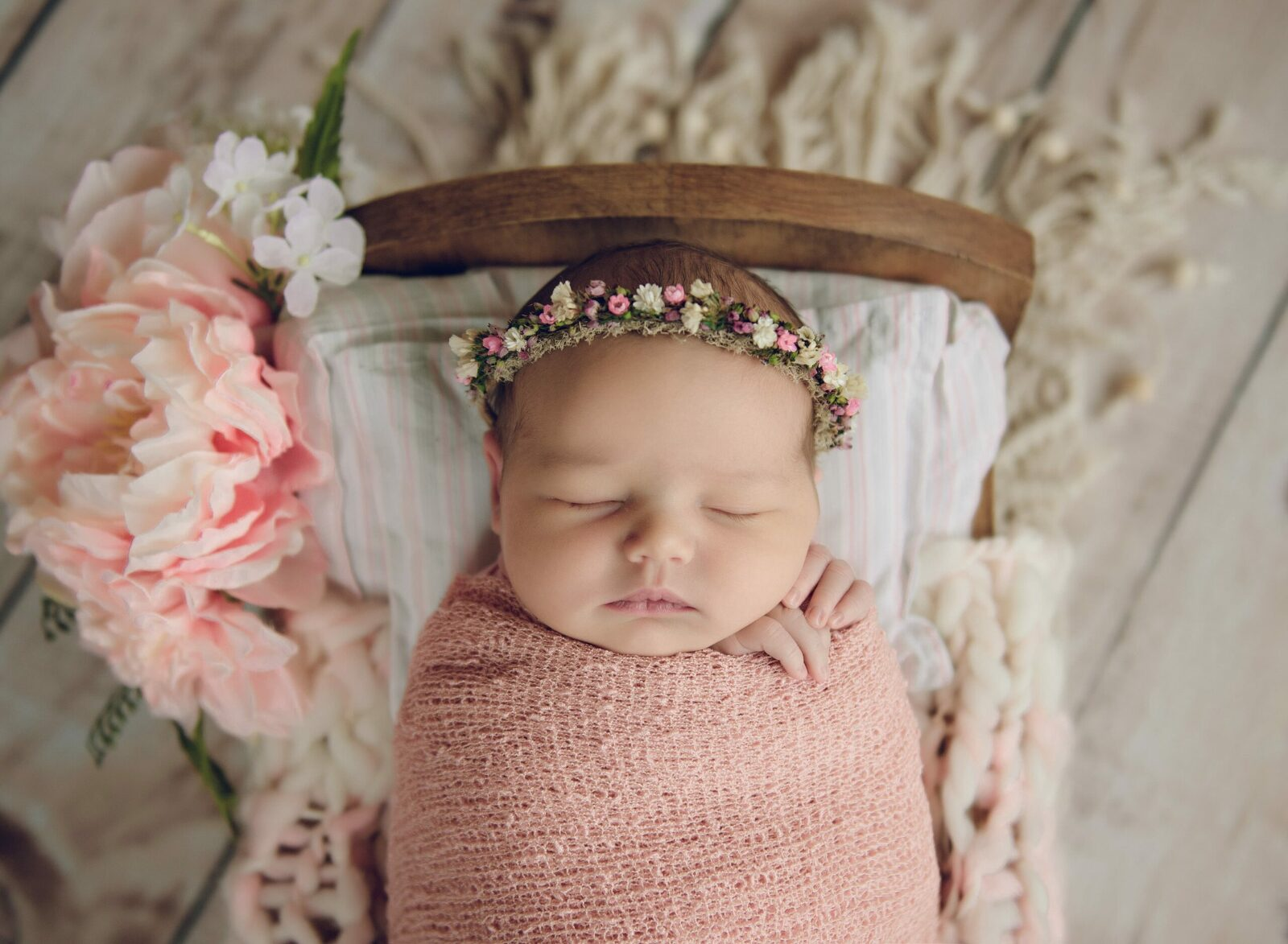 newborn baby girl in a wooden crib wearing a pink floral halo