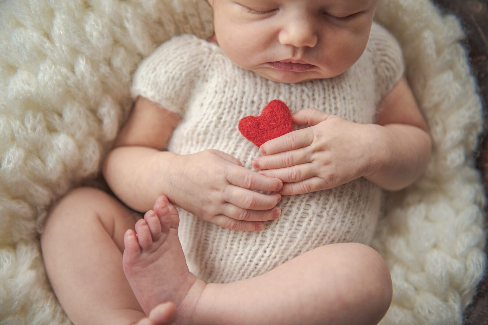 newborn baby girl in bowl holding a red felted heart