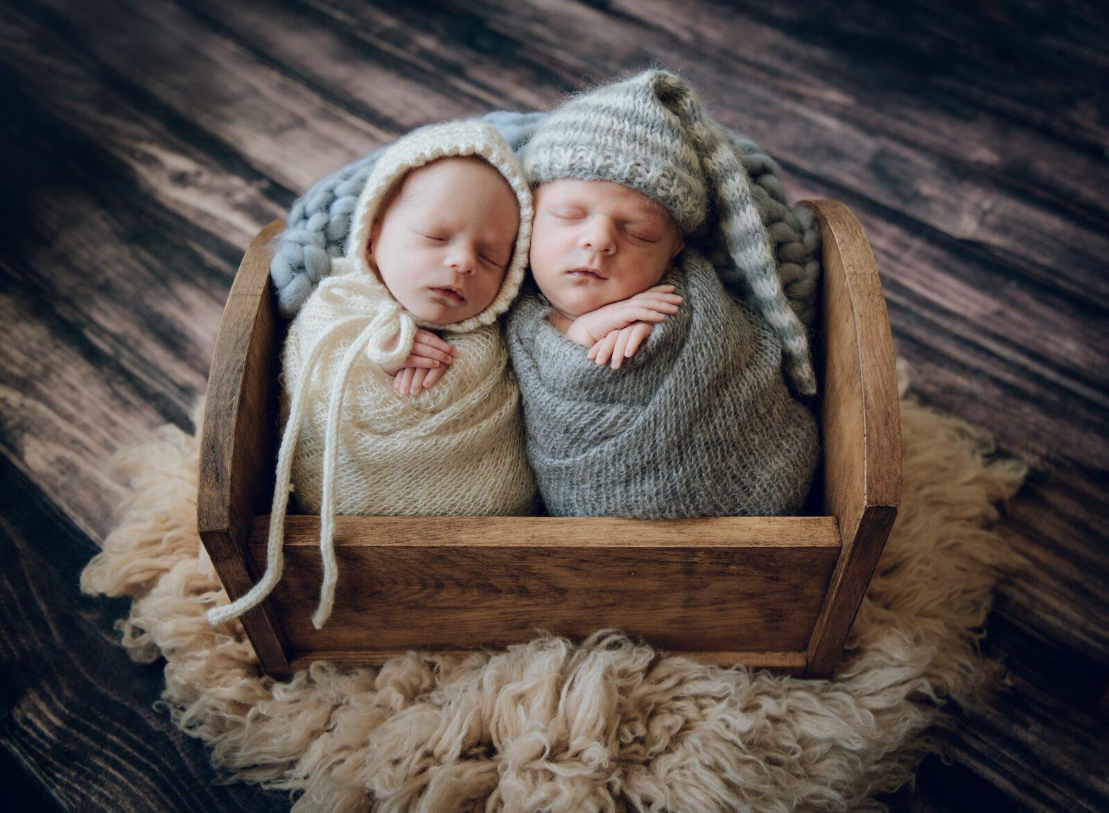newborn twin baby sister and brother potato sack pose in crib