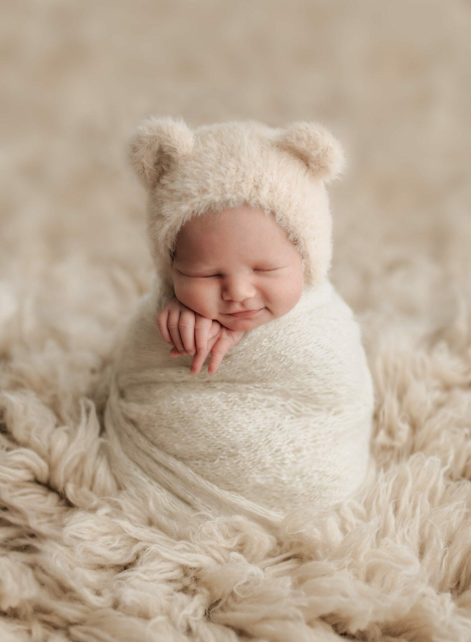newborn baby boy in potato sack pose on ivory flokati fur with fuzzy bear bonnet