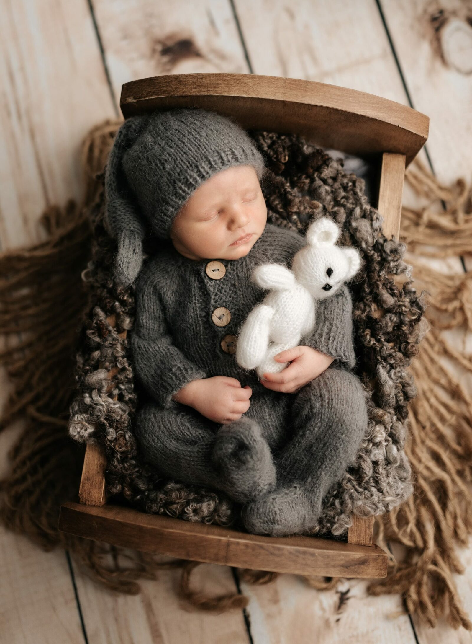 newborn baby boy in crib with sleepy cap and white teddy bear