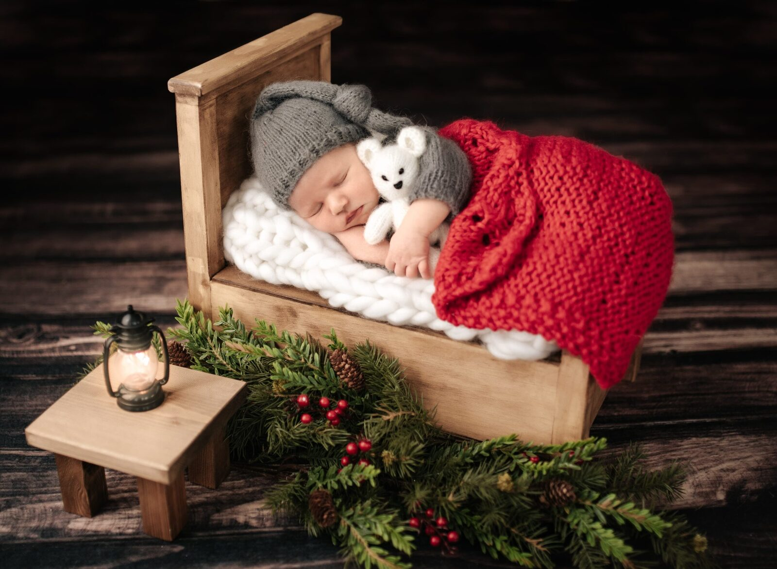 newborn baby boy sleeping in tiny bed holding white bear with tiny table and glowing lantern christmas
