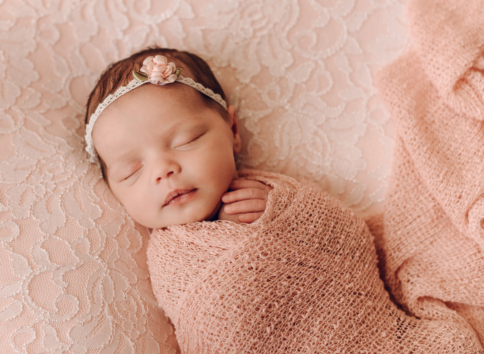 newborn baby girl on peach lace blanket with peach wrap and floral headband