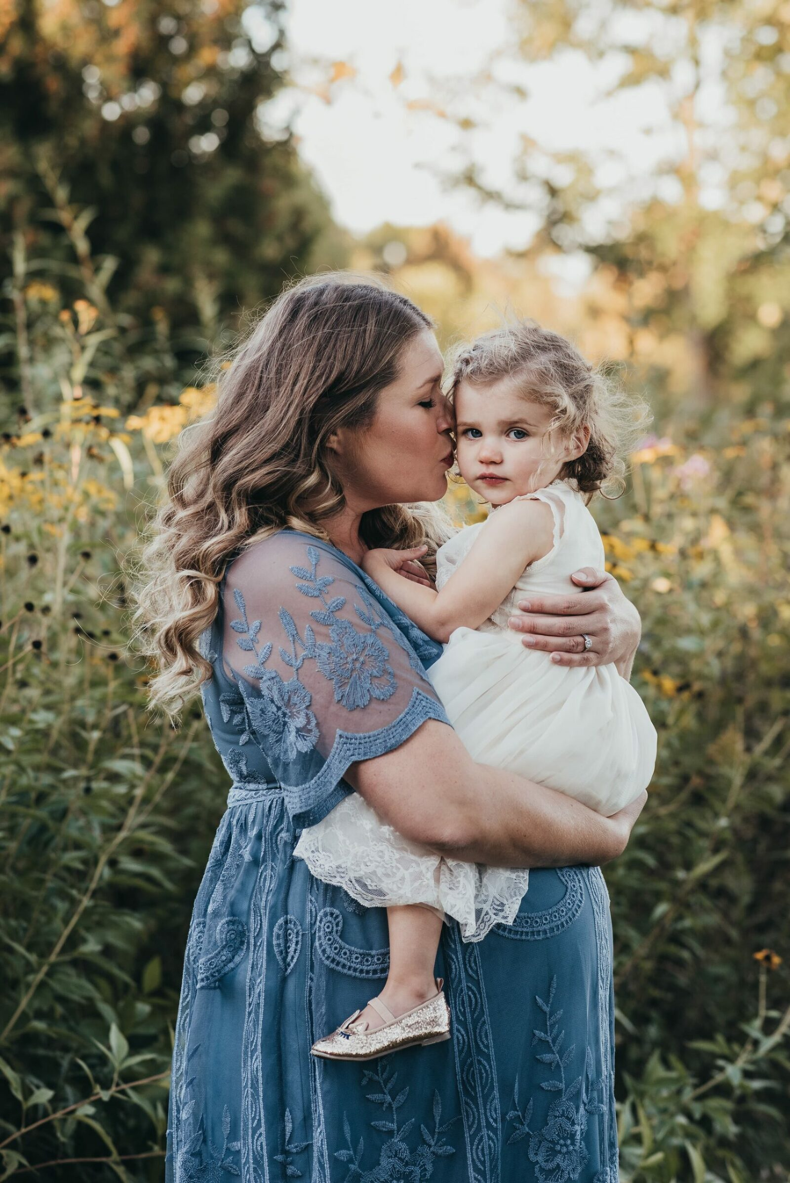 pregnant mother in lacy blue dress holding her daughter and kissing her cheek