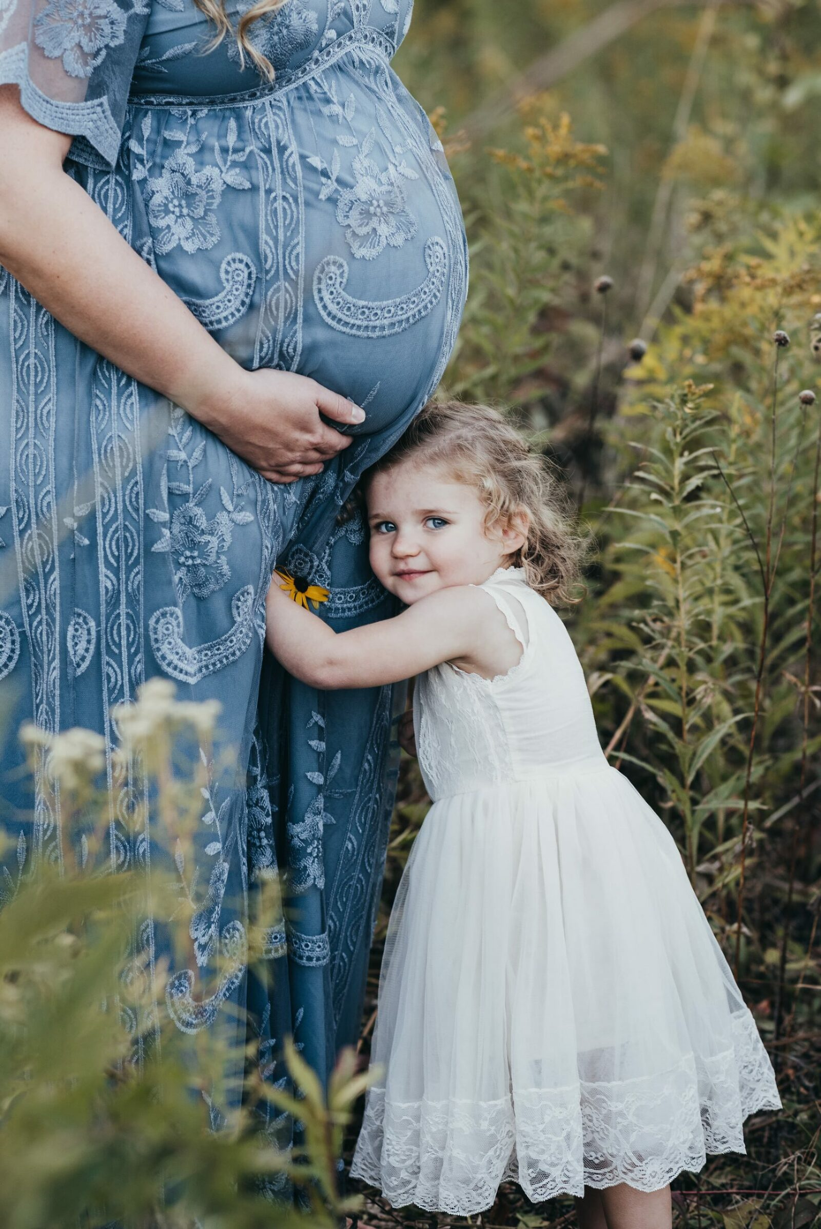 pregnant mother holding her belly in lacy blue dress with daughters head under the belly
