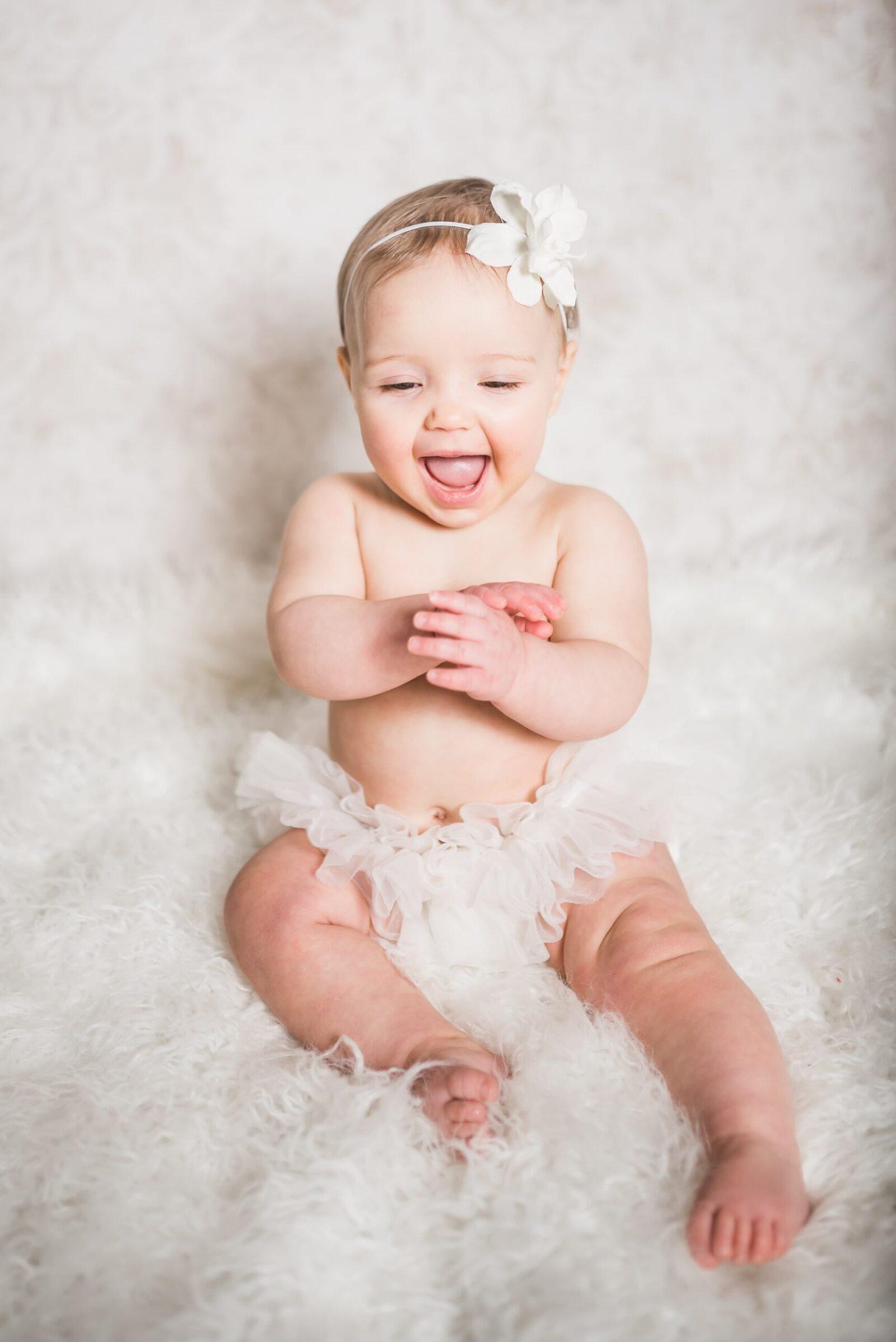 baby girl in tutu on white fur laughing