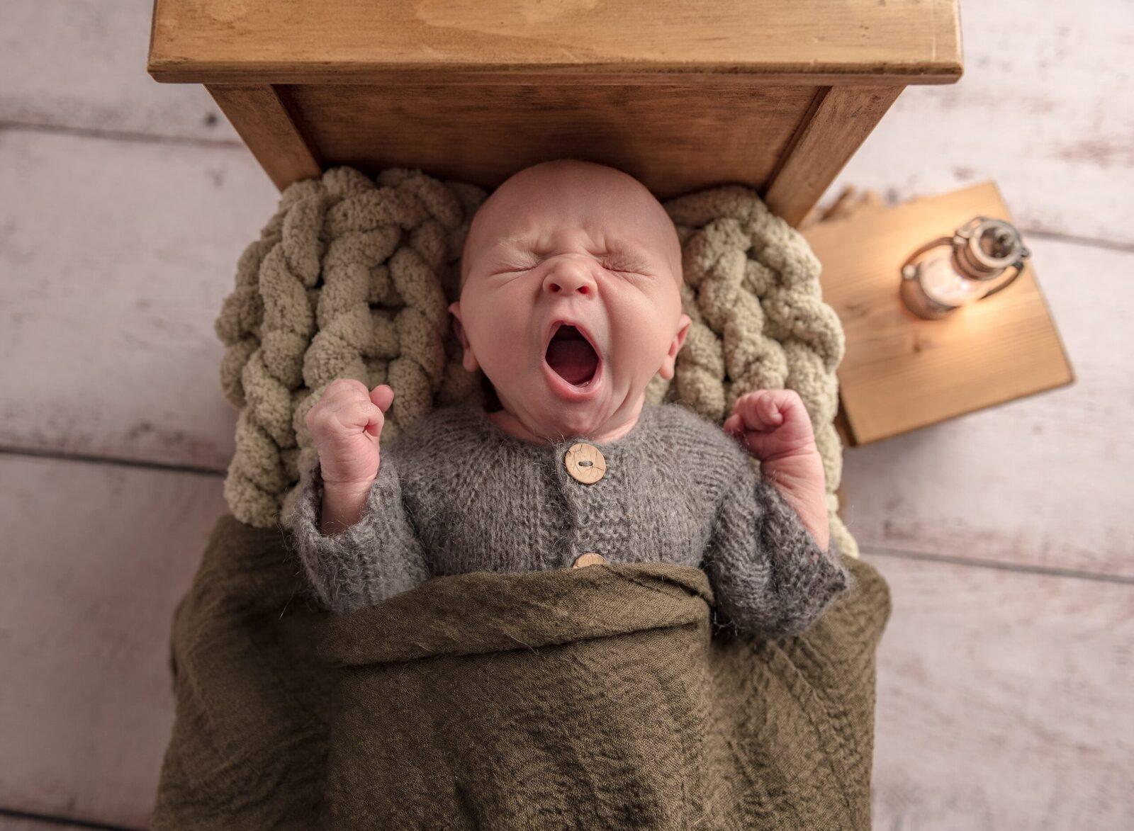 newborn baby boy in little bed yawning