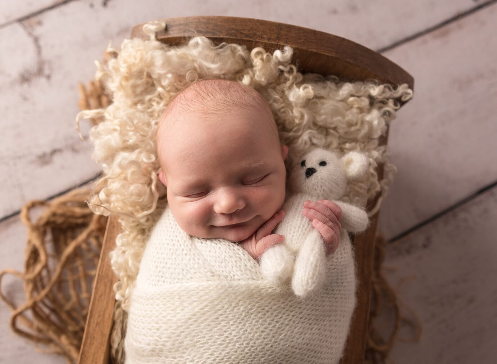 newborn baby boy in wooden cradle with white bear lovie